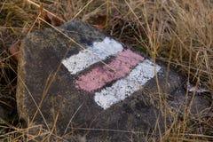 Κόκκινο και άσπρο σύμβολο πορειών πεζοπορώ στην πέτρα Στοκ Εικόνα