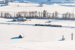 Κόκκινο και άσπρο τραίνο που περνά τους χιονισμένους τομείς σε ένα φυσικό τοπίο χειμερινών βουνών, ορεινός όγκος Dachstein, περιο στοκ φωτογραφίες με δικαίωμα ελεύθερης χρήσης