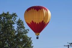 Κόκκινο και κίτρινο μπαλόνι ζεστού αέρα που κατεβαίνει κοντά σε ένα δέντρο στοκ εικόνες