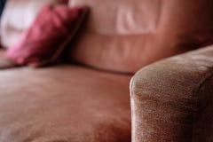 Κόκκινο και καφετί armrest ενός καναπέ με το μαξιλάρι Στοκ εικόνα με δικαίωμα ελεύθερης χρήσης