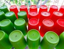 Κόκκινο και πράσινο πλαστικό φλυτζάνι Στοκ Φωτογραφίες