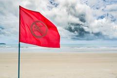 Κόκκινο καμία προειδοποίηση σημαιών κολύμβησης για τον τουρίστα να μην κολυμπήσει κατά τη διάρκεια του stor Στοκ Φωτογραφία