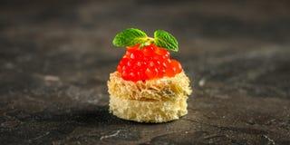 Κόκκινο καναπεδάκια ή σάντουιτς χαβιαριών με τα κόκκινα ψάρια σολομών πρόχειρων φαγητών, θαλασσινά τρόφιμα μπουλεττών ανασκόπησης στοκ φωτογραφία με δικαίωμα ελεύθερης χρήσης