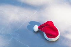 Κόκκινο καπέλο Άγιου Βασίλη στη ημέρα των Χριστουγέννων στο επιτραπέζιο υπόβαθρο Στοκ Εικόνα