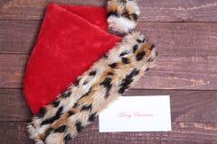 Κόκκινο καπέλο Santa με την κάρτα που απομονώνεται στο ξύλινο υπόβαθρο Στοκ φωτογραφία με δικαίωμα ελεύθερης χρήσης