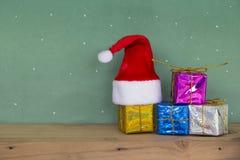 Κόκκινο καπέλο Santa με το ζωηρόχρωμο κιβώτιο δώρων στο ξύλινο floorand Στοκ εικόνα με δικαίωμα ελεύθερης χρήσης