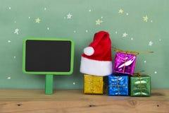 Κόκκινο καπέλο Santa με το ζωηρόχρωμο κιβώτιο δώρων στο ξύλινο floorand Στοκ Φωτογραφία