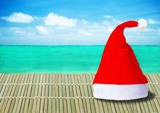 Κόκκινο καπέλο Άγιου Βασίλη στο ωκεάνιο υπόβαθρο Στοκ φωτογραφίες με δικαίωμα ελεύθερης χρήσης