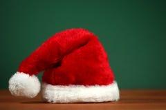 Κόκκινο καπέλο Santa με το διάστημα αντιγράφων στο πράσινο και ξύλινο υπόβαθρο στοκ εικόνες με δικαίωμα ελεύθερης χρήσης