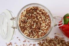 Κόκκινο καφετί ρύζι σε ένα διαφανές βάζο με το ζυγό καπακιών, άσπρο υπόβαθρο Στοκ εικόνες με δικαίωμα ελεύθερης χρήσης