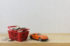 Κόκκινο καλαθιών με το αυτοκίνητο και τα νομίσματα Στοκ Εικόνες