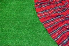 Κόκκινο κενό κάλυμμα ταρτάν πικ-νίκ στη φρέσκια τακτοποιημένη χλόη Στοκ φωτογραφίες με δικαίωμα ελεύθερης χρήσης