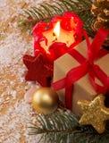 Κόκκινο κερί με τη σφαίρα Χριστουγέννων στο ατμοσφαιρικό φως Στοκ Φωτογραφίες