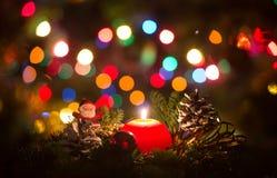 Κόκκινο κερί Χριστουγέννων με τα φω'τα Χριστουγέννων που θολώνονται Στοκ εικόνες με δικαίωμα ελεύθερης χρήσης