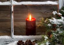 Κόκκινο κερί Χριστουγέννων με το χιονισμένα εγχώριο παράθυρο και το δέντρο πεύκων Στοκ εικόνα με δικαίωμα ελεύθερης χρήσης