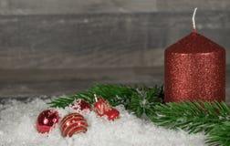 Κόκκινο κερί Χριστουγέννων στο χιόνι με τις σφαίρες Χριστουγέννων Στοκ εικόνες με δικαίωμα ελεύθερης χρήσης