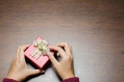 Κόκκινο κιβώτιο δώρων με το χέρι στο ξύλινο υπόβαθρο Στοκ φωτογραφία με δικαίωμα ελεύθερης χρήσης