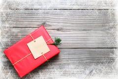Κόκκινο κιβώτιο δώρων χριστουγεννιάτικου δώρου στο εκλεκτής ποιότητας ξύλινο υπόβαθρο με snowflake Στοκ Εικόνες