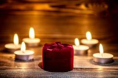 Κόκκινο κιβώτιο με ένα δαχτυλίδι στο υπόβαθρο του καψίματος του μικρού κεριού Στοκ φωτογραφία με δικαίωμα ελεύθερης χρήσης