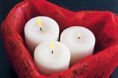 Κόκκινο κιβώτιο στη μορφή καρδιών και τρία καίγοντας άσπρα κεριά σε ένα μπλε υπόβαθρο Στοκ Εικόνες