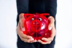 Κόκκινο κιβώτιο χρημάτων χοίρων στα χέρια ενός σκοτεινός-ξεφλουδισμένου κοριτσιού στοκ εικόνες