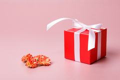 Κόκκινο κιβώτιο δώρων με τα λουλούδια τόξων και άνοιξη Στοκ Φωτογραφία