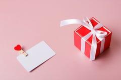 Κόκκινο κιβώτιο δώρων με το πρότυπο καρτών τόξων και πίστωσης/επίσκεψης με το σφιγκτήρα Στοκ Εικόνα