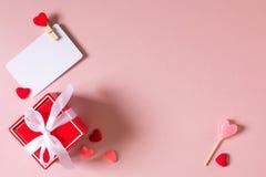 Κόκκινο κιβώτιο δώρων με το πρότυπο τόξων, καρτών πίστωσης/επίσκεψης με το σφιγκτήρα, την καραμέλα και τις μικρές καρδιές Στοκ φωτογραφία με δικαίωμα ελεύθερης χρήσης