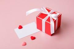 Κόκκινο κιβώτιο δώρων με το πρότυπο τόξων, καρτών πίστωσης/επίσκεψης και τις μικρές καρδιές Στοκ Εικόνα