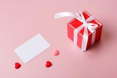 Κόκκινο κιβώτιο δώρων με το πρότυπο τόξων, καρτών πίστωσης/επίσκεψης και τις μικρές καρδιές Στοκ Φωτογραφίες