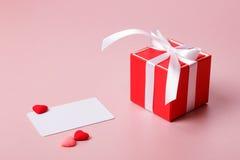 Κόκκινο κιβώτιο δώρων με το πρότυπο τόξων, καρτών πίστωσης/επίσκεψης και τις μικρές καρδιές Στοκ φωτογραφίες με δικαίωμα ελεύθερης χρήσης