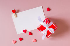 Κόκκινο κιβώτιο δώρων με το τόξο, πρότυπο χαρτικών/φωτογραφιών με το σφιγκτήρα και μικρές καρδιές Στοκ εικόνες με δικαίωμα ελεύθερης χρήσης