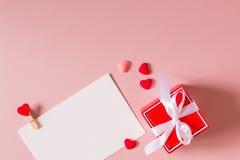 Κόκκινο κιβώτιο δώρων με το τόξο, πρότυπο χαρτικών/φωτογραφιών με το σφιγκτήρα και μικρές καρδιές Στοκ Φωτογραφίες