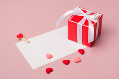 Κόκκινο κιβώτιο δώρων με το τόξο, πρότυπο χαρτικών/φωτογραφιών με το σφιγκτήρα και μικρές καρδιές Στοκ φωτογραφία με δικαίωμα ελεύθερης χρήσης
