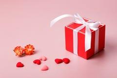 Κόκκινο κιβώτιο δώρων με το τόξο, τα λουλούδια άνοιξη και τις μικρές καρδιές επάνω Στοκ Εικόνα