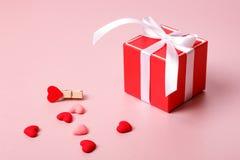 Κόκκινο κιβώτιο δώρων με το τόξο, τα λουλούδια άνοιξη, το σφιγκτήρα και τις μικρές καρδιές Στοκ Εικόνες