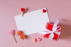 Κόκκινο κιβώτιο δώρων με το τόξο, τα χαρτικά/το πρότυπο φωτογραφιών/καρτών με το σφιγκτήρα, τις μικρές καρδιές, την καραμέλα, και Στοκ Εικόνα