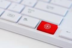 Κόκκινο κλειδί με το σύμβολο εικονιδίων συμβόλων στόχων στο άσπρο πληκτρολόγιο lap-top Στοκ Εικόνες