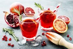 Κόκκινο κοκτέιλ με το πορτοκάλι και το ρόδι αίματος Αναζωογονώντας θερινό ποτό Απεριτίφ διακοπών για τη γιορτή Χριστουγέννων στοκ εικόνα με δικαίωμα ελεύθερης χρήσης