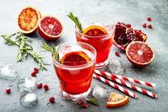 Κόκκινο κοκτέιλ με το πορτοκάλι και το ρόδι αίματος Αναζωογονώντας θερινό ποτό Απεριτίφ διακοπών για τη γιορτή Χριστουγέννων στοκ εικόνες