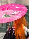 Κόκκινο κορίτσι τρίχας με την παραδοσιακή ιαπωνική ρόδινη ομπρέλα Wagasa Στοκ φωτογραφίες με δικαίωμα ελεύθερης χρήσης