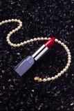 Κόκκινο κραγιόν με ένα περιδέραιο μαργαριταριών Στοκ Εικόνα