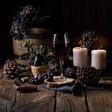 Κόκκινο κρασί από ένα βαρέλι με τα σταφύλια και ένα ποτήρι του κρασιού Στοκ Φωτογραφία