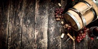 κόκκινο κρασί γυαλιού ανασκόπησης Ένα βαρέλι με το κόκκινο κρασί και πρόσφατα τα σταφύλια Στοκ Φωτογραφία