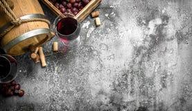 κόκκινο κρασί γυαλιού ανασκόπησης Ένα βαρέλι με το κόκκινο κρασί και τα φρέσκα σταφύλια Στοκ Φωτογραφία
