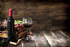 κόκκινο κρασί γυαλιού ανασκόπησης Κόκκινο κρασί με ένα κιβώτιο των σταφυλιών Στοκ Φωτογραφία