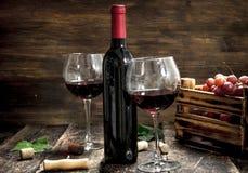 κόκκινο κρασί γυαλιού ανασκόπησης Κόκκινο κρασί με ένα κιβώτιο των σταφυλιών Στοκ φωτογραφίες με δικαίωμα ελεύθερης χρήσης