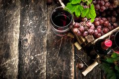 κόκκινο κρασί γυαλιού ανασκόπησης Κόκκινο κρασί με ένα κιβώτιο των σταφυλιών Στοκ Εικόνα