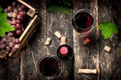 κόκκινο κρασί γυαλιού ανασκόπησης Κόκκινο κρασί με ένα κιβώτιο των σταφυλιών Στοκ Φωτογραφίες