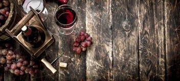 κόκκινο κρασί γυαλιού ανασκόπησης Κόκκινο κρασί με τα γυαλιά με τα σταφύλια Στοκ φωτογραφίες με δικαίωμα ελεύθερης χρήσης